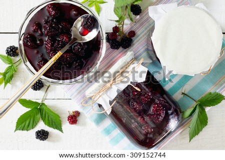 Blackberries, canned in juice cans on a wooden table - stock photo