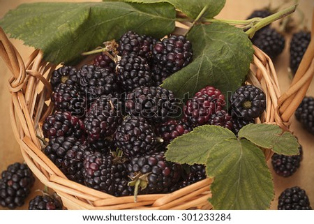 Blackberries in a basket on wooden background Healthy food. Diet concept.