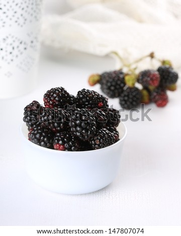 Blackberries in a bowl on white wooden background