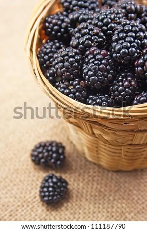 Blackberries in basket on burlap background - stock photo