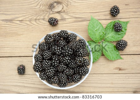 blackberries in bowl and leaves, top view - stock photo