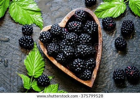 Blackberries in bowl in the shape of a heart, a top view - stock photo