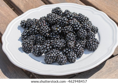 Blackberries on the plate on the old wooden table.
