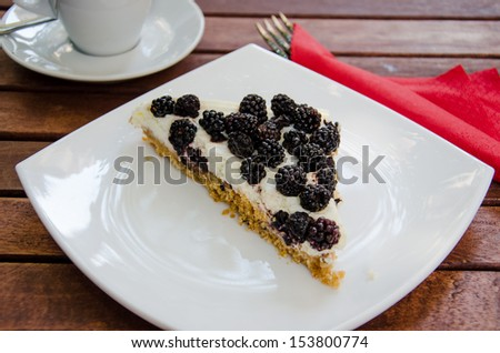 Blackberry cheesecake with coffee standing at the wooden table - stock photo