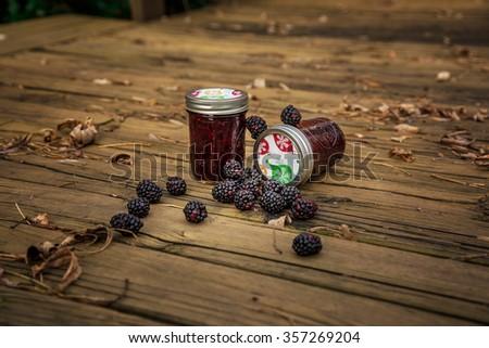 Blackberry jam in Jars, focus on the lid - stock photo