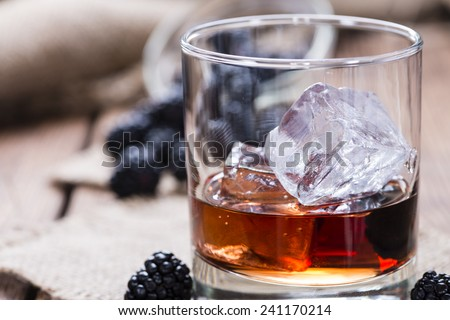 Blackberry Liqueur (as shot) on wooden background - stock photo