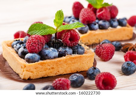 Blackberry tart with raspberries, mint and anise star - stock photo