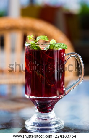 Blackberry tea in a glass cup. Decorated with mint leaves - stock photo