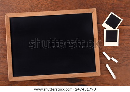 Blackboard and chalk with photo frames on brown background. - stock photo