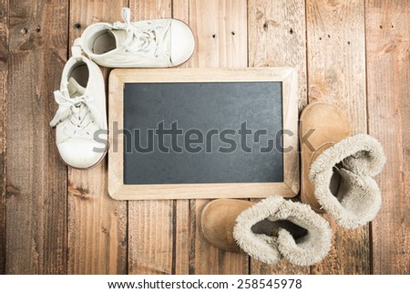 Blackboard and children's shoes - stock photo