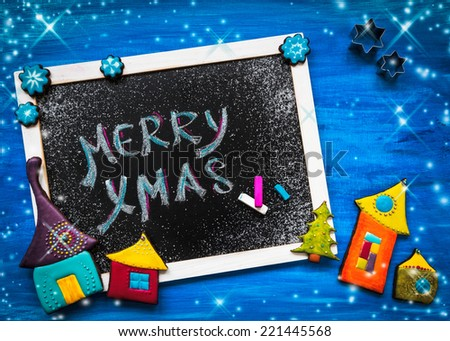 Blackboard decorated with colorful christmas cookies  - stock photo