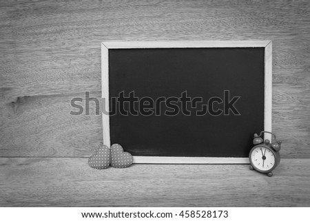 blackboard decoration with clock and two heart on wooden background