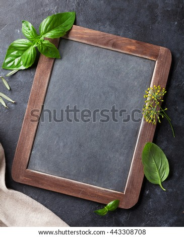 Blackboard for your text and fresh garden herbs on stone table. Basil, rosemary, dill. Cooking ingredients. Top view with copy space - stock photo