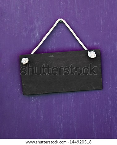 blackboard hanging on the purple door - stock photo