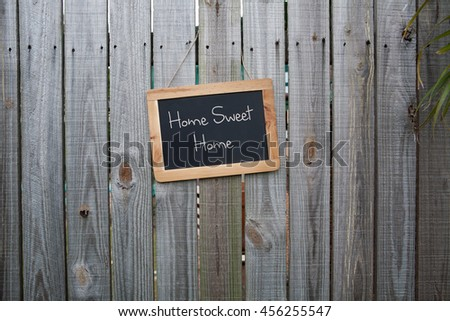 Blackboard Home sweet home sign on wooden fence