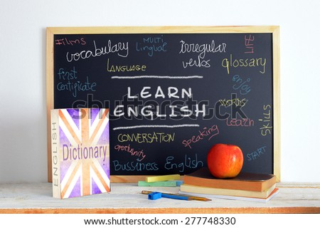Blackboard in an English class. British English. Some books and school stuff for studying English language in a classroom. - stock photo