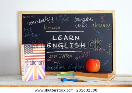 Blackboard in an English class. Some books and school stuff for studying English language in a classroom. - stock photo