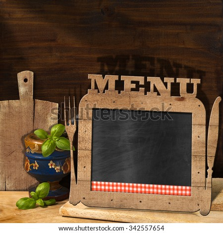 Blackboard Menu in the Kitchen / Empty blackboard with wooden frame, text Menu, fork and knife in the kitchen with mortar and pestle with basil leaves and cutting boards. Template for food menu - stock photo