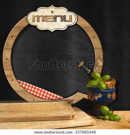Blackboard Menu in the Kitchen / Empty round blackboard with wooden frame and label with text Menu, in the kitchen with mortar and pestle with basil leaves and cutting boards. Template for food menu - stock photo