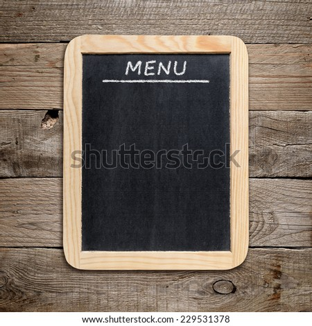 Blackboard menu on old wooden background - stock photo