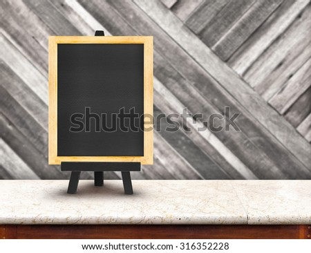 Blackboard menu with easel on marble table with blur diagonal wood wall at restaurant background, Copy space for adding your content
