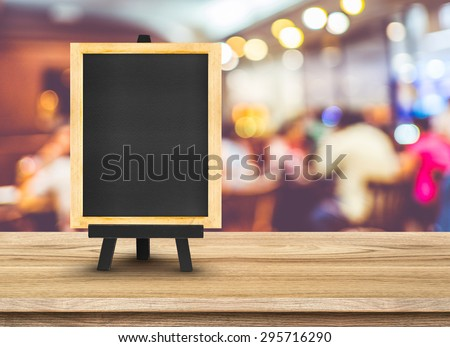Blackboard menu with easel on wooden table with blur restaurant background, Copy space for adding your content - stock photo