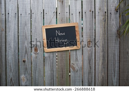 Blackboard Now Hiring sign on wooden fence - stock photo
