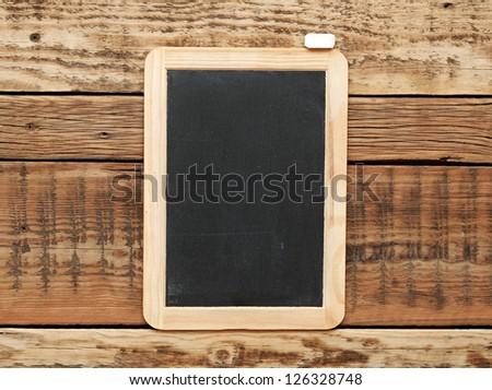Blackboard on the wood wall. - stock photo