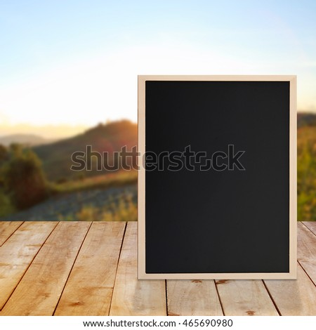 Blackboard on top of wooden table with nature background