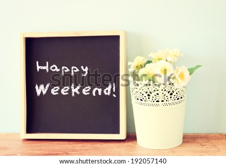 blackboard over wooden shelf with the phrase happy weekend - stock photo