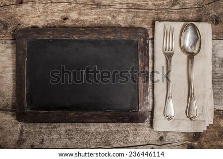 Blackboard with spoon and fork over wooden background - stock photo