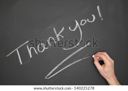 "Blackboard with ""Thank You"" wrote on it with a hand."