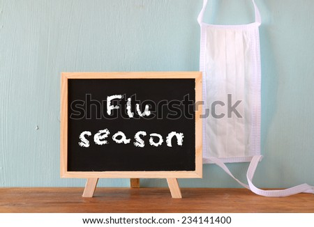 blackboard with the phrase flu season written on it and face mask - stock photo