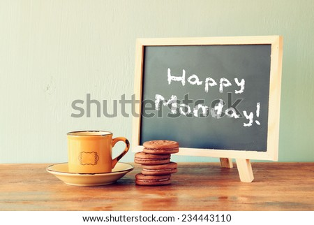 blackboard with the phrase happy monday next to cup of coffee and cookies - stock photo