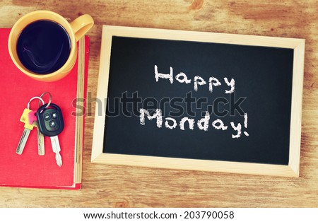 blackboard with the phrase happy monday written on it, coffee cup and car keys. filtered image. - stock photo