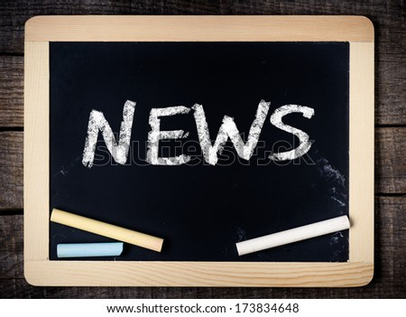 Blackboard with the text News on wooden background - stock photo