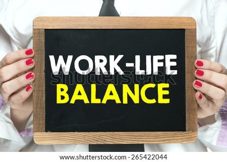 Blackboard with work-life balance. Hands holding blackboard with handwritten work-life balance - stock photo