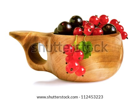 Blackcurrant and redcurrant berries in traditional finnish birch cup, isolated over white background.