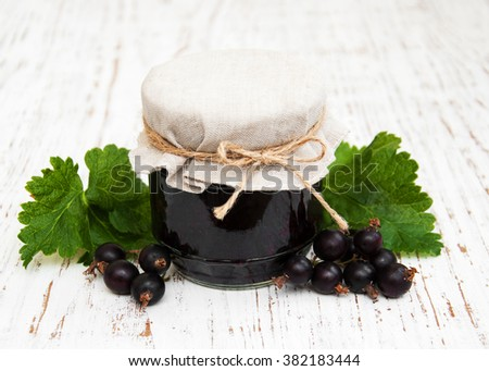 blackcurrants jam with fresh berries on a wooden background - stock photo
