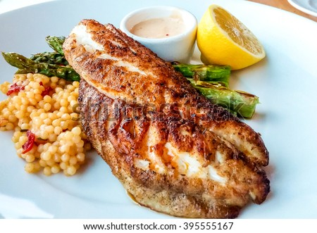 Blackened fish dinner with couscous asparagus and lemon