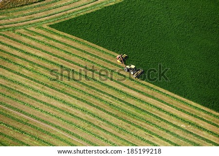Blackfoot, Idaho, USA Aug. 7, 2012 An aerial view of farm machinery harvesting hay in an alfalfa field - stock photo