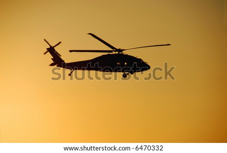 Blackhawk helicopter against a sunset sky - stock photo