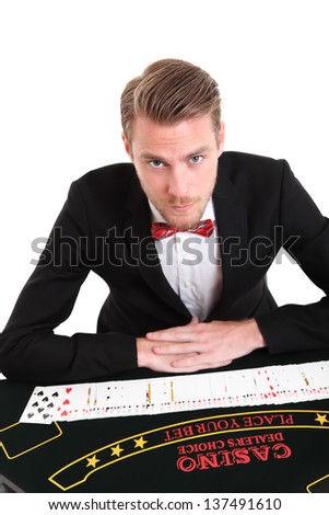 Blackjack dealer in a suit and bowtie with cards. White background. - stock photo