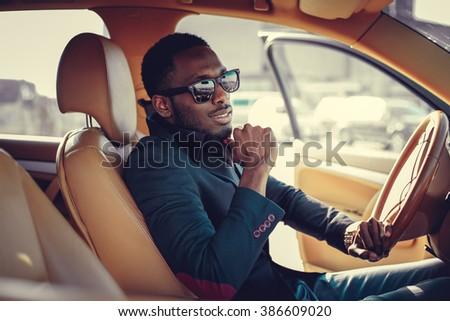 Blackman in sunglasses driving a car. - stock photo