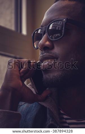 Blackman in sunglasses talking on smartphone. - stock photo