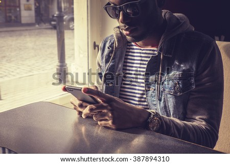 Blackman in sunglasses using smartphone. - stock photo