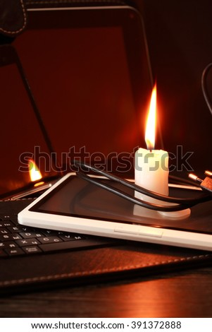 Blackout concept. Lighting candle on laptop and tablet - stock photo