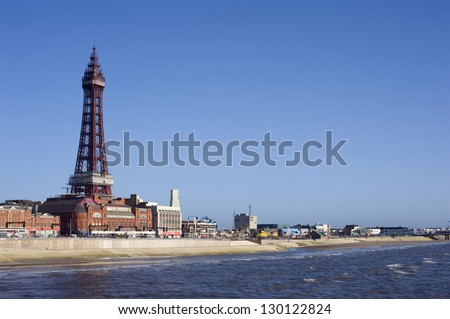 Blackpool waterfront and beach with Blackpool Tower, a historical Victorian lattice structure, overlooking the ocean - stock photo