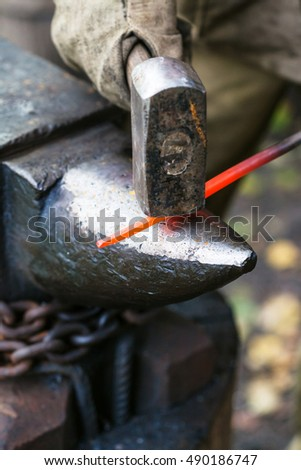 Blacksmith forges red hot steel rod on anvil in outdoor rural smithy