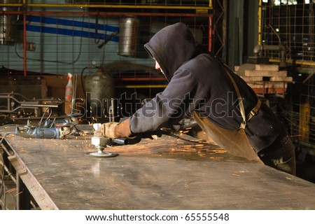 Blacksmith grinding welding residue from welding table - stock photo